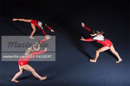 Female gymnasts practicing floor routine