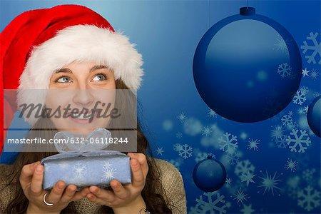 Jeune femme en chapeau de Santa holding Noël cadeau, portrait