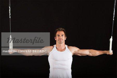 Male gymnast holding onto gymnastics rings