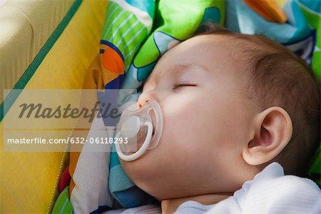 Petite fille avec une sucette dans sa bouche la sieste