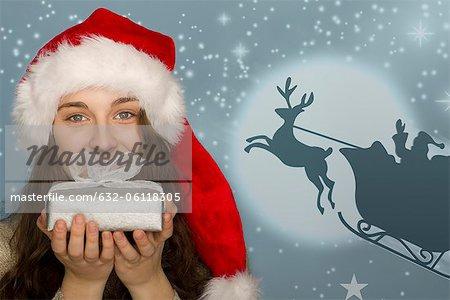 Jeune femme en bonnet tenant le cadeau de Noël, graphique du traîneau du père Noël en arrière-plan