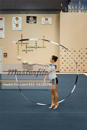 Teenage girl gymnast practicing rhythmic gymnastics, twirling ribbon
