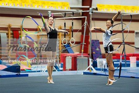 Teenage girl gymnasts practicing rhythmic gymnastics, twirling ribbons