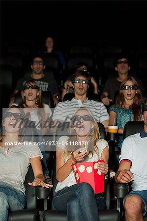 Public portant des lunettes 3D en salle de cinéma avec des expressions sur les visages choquées
