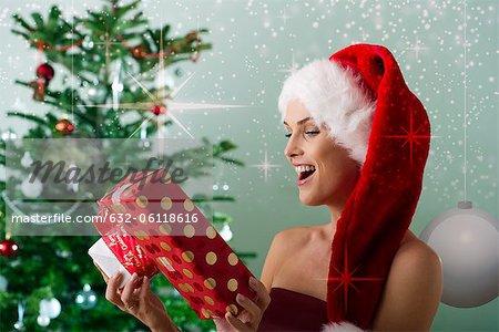 Woman wearing Santa hat, looking at Christmas gifts