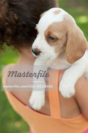 Fille portant des chiots beagle sur l'épaule