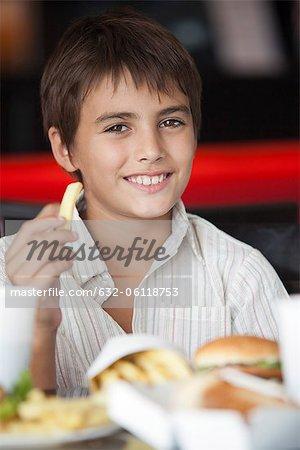 Boy eating fast food, portrait
