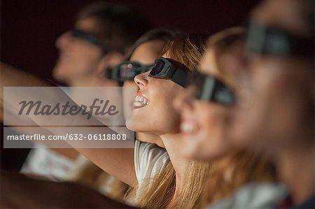 Femme portant 3D verres dans la salle de cinéma, bras de tendre la main