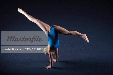 Gymnast doing handstand with legs split