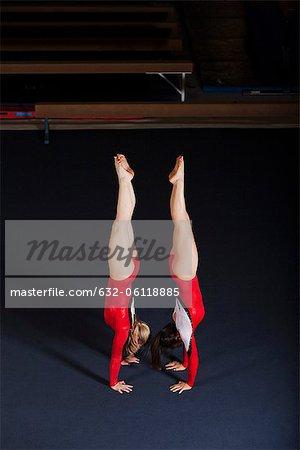 Female gymnasts performing handstands back to back