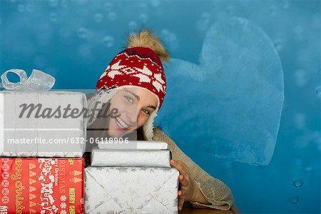 Jeune femme avec des piles de cadeaux de Noël, portrait