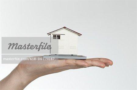 main de femme avec maison de jouet