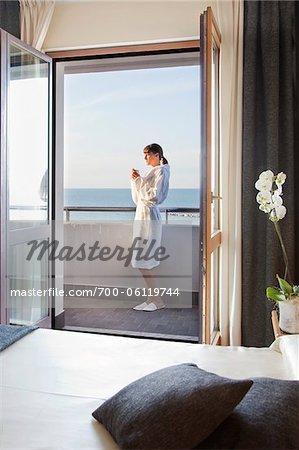 Frau mit Kaffee am Morgen auf Balkon