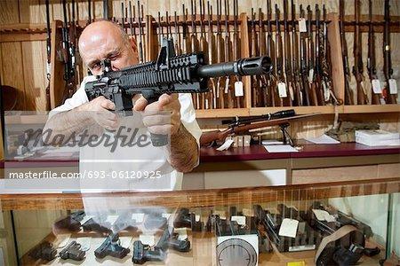 Mature marchand visant avec fusil en armurerie