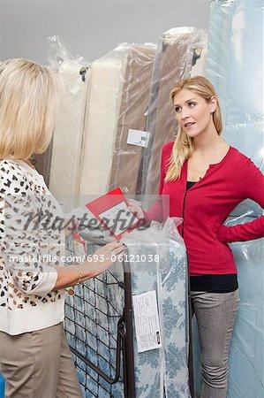 Junge Frau hält Preisliste beim Betrachten der Mutter im Möbelhaus