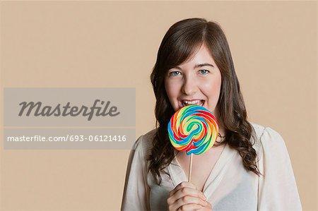 Portrait d'une belle jeune femme avec sucette sur fond coloré
