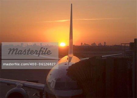 Jet on tarmac at sunrise Dallas skyline in background