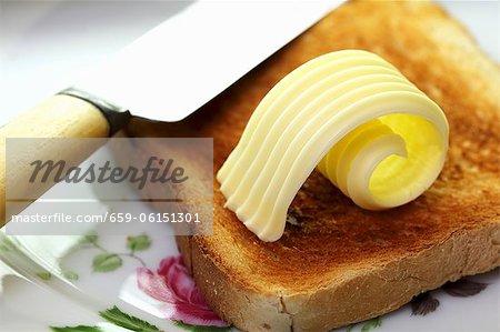 Eine Scheibe Toast mit Butter ein Kringel