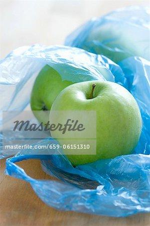 Pommes vertes dans des sacs en plastique