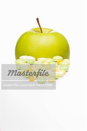 Comprimés de vitamines et une pomme Golden Delicious