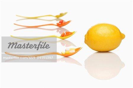 Cuillères avec les comprimés de vitamines et de citron