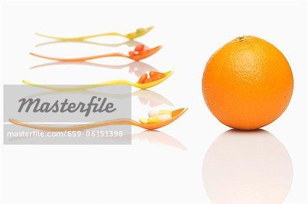 Cuillères avec les comprimés de vitamines et une orange