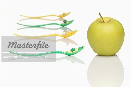 Cuillères avec les comprimés de vitamines et une pomme verte