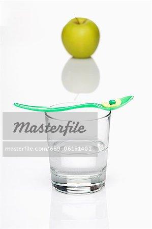 Un comprimé de vitamine sur une cuillère sur le dessus un verre d'eau avec une pomme verte en arrière-plan