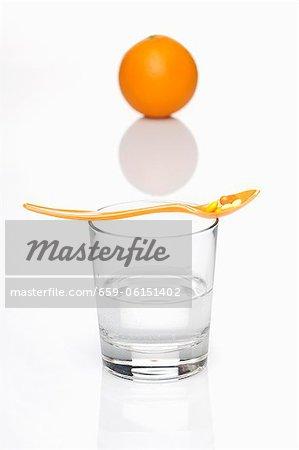 Comprimés de vitamines sur une cuillère sur le dessus un verre d'eau avec une orange dans le fond