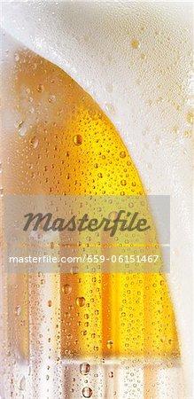 Mousse de la bière qui coule au-dessus d'un verre (gros plan)