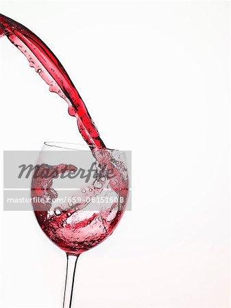 Gießen in einem Glas aus Flasche Rotwein