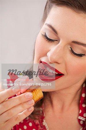 Une jeune fille mangeant un muffin aux fraises