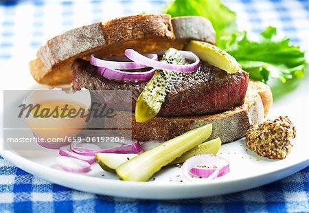 Ein Rindfleisch-Sandwich mit Gurken, Ei, Zwiebel und Senf