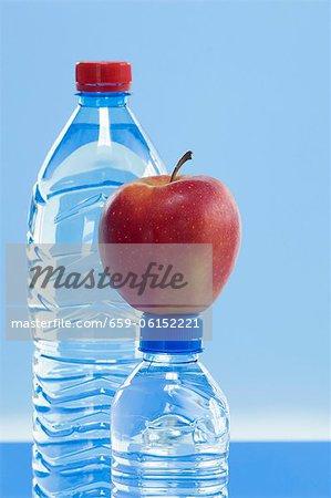 Bouteilles d'eau minérale et une pomme Elstar