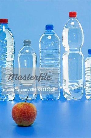 Une pomme Elstar et plusieurs bouteilles d'eau minérale