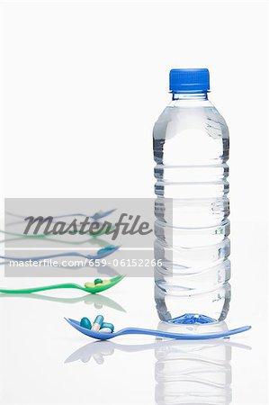Une bouteille d'eau minérale et des pilules de vitamines sur cuillères