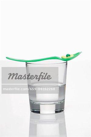 Une pilule de vitamine sur une cuillère sur un verre d'eau