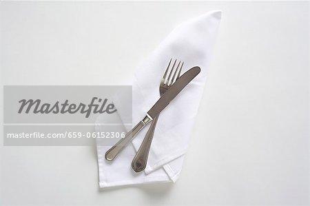 Besteck auf eine weiße Serviette, von oben gesehen