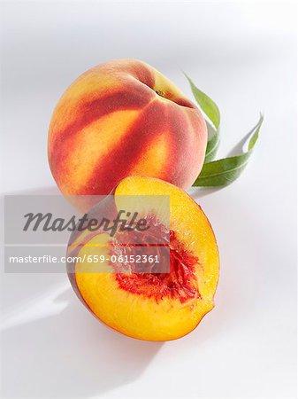 Eine ganze und halbierte Pfirsich