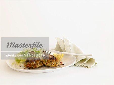 Crab Cakes mit Side Salat auf einem Teller; Stoff-Serviette