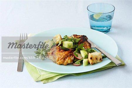 Gegrillte Hühnerkeule, gekrönt mit einem Frühlings-Salat mit Croutons; Glas Wasser mit Zitrone