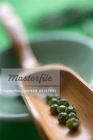 Grains de poivre verts dans une boule en bois