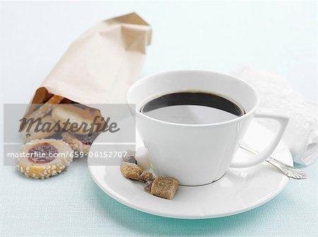 Eine Tasse Kaffee mit Zucker und einen Beutel mit Gebäck