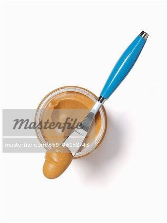 Glas Erdnussbutter; Messer mit Erdnussbutter drauf; Von oben; Weißer Hintergrund