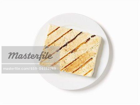 Gegrillter Tofu auf einem weißen Teller; Weißer Hintergrund; Von oben