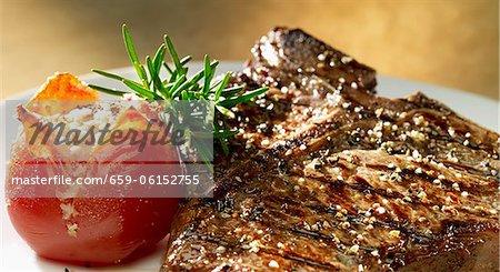 T-bone-Steak vom Grill mit Tomaten und Rosmarin