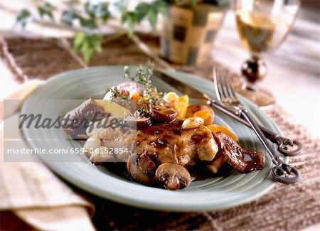 Poulet balsamique aux champignons sur une plaque. Couteau et fourchette
