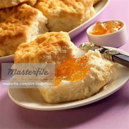 Keks mit Orange Marmelade auf einem Teller; Messer; Teller mit Gebäck