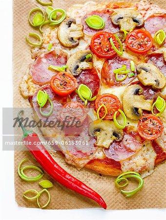 Pizza au salami, champignons, tomates, poireaux, mozzarella et piments