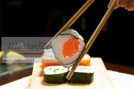 Eine Hand hält eine Maki-Sushi in Stäbchen